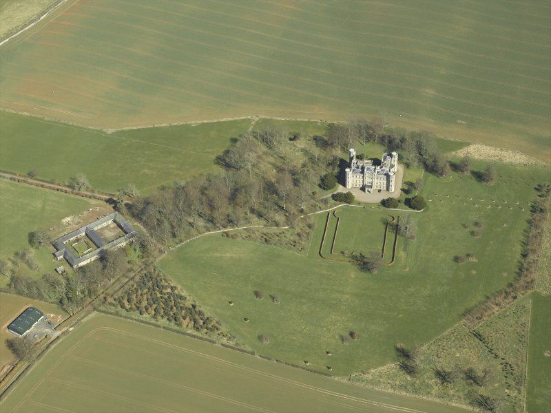 Oblique aerial view centred on the country house, stable block and landscaped gardens, taken from the SW.