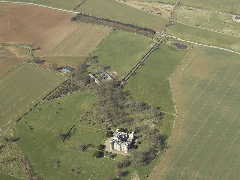 Oblique aerial view centred on the country house, stable block and landscaped gardens with the gate and gate lodge adjacent, taken from the SE.
