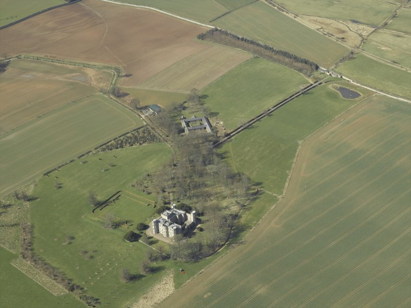 Oblique aerial view centred on the country house, stable block and landscaped gardens with the gate and gate lodge adjacent, taken from the ESE.
