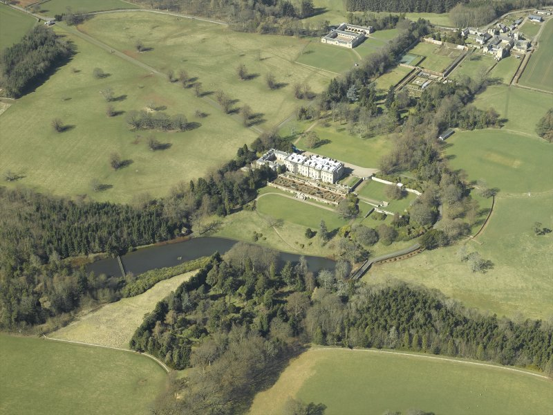 General oblique aerial view centred on the country house, garden, stable, footbridge and lake, taken from the SE.
