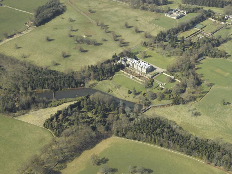 General oblique aerial view centred on the country house, garden, stable, footbridge and lake, taken from the E.