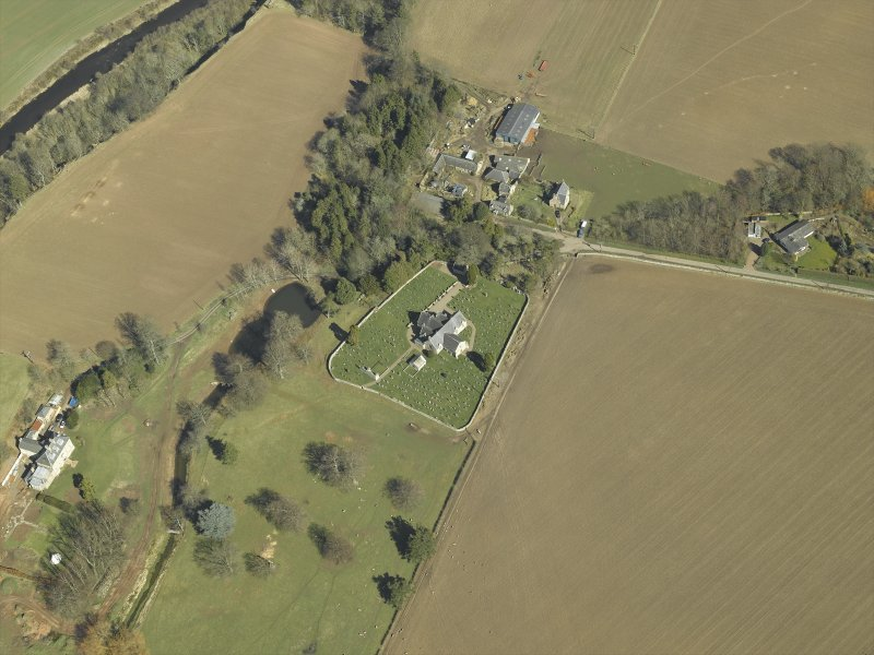 General oblique aerial view centred on the churches and burial-ground with the country house, school, farmhouse and farmsteading adjacent, taken from the SW.
