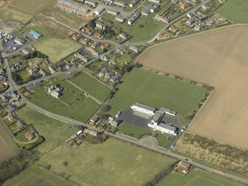 Oblique aerial view centred on the school with the church, burial ground and dovecot adjacent, taken from the SE.
