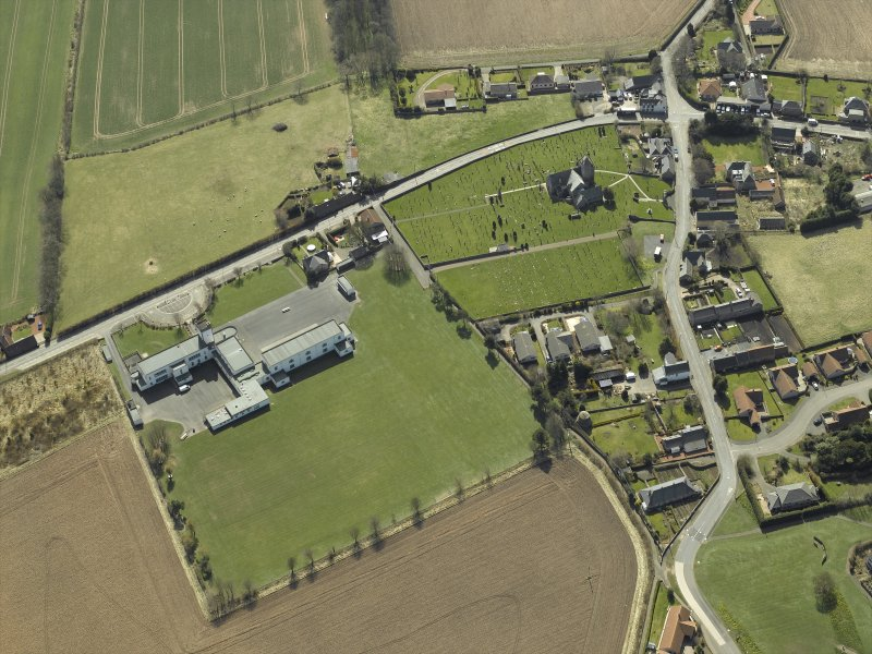 Oblique aerial view centred on the school with the church, burial ground and dovecot adjacent, taken from the N.
