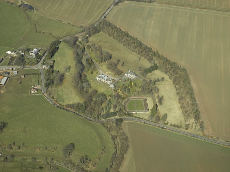 Oblique aerial view centred on the country house and walled garden with the gate-lodge and road bridge adjacent, taken from the S.