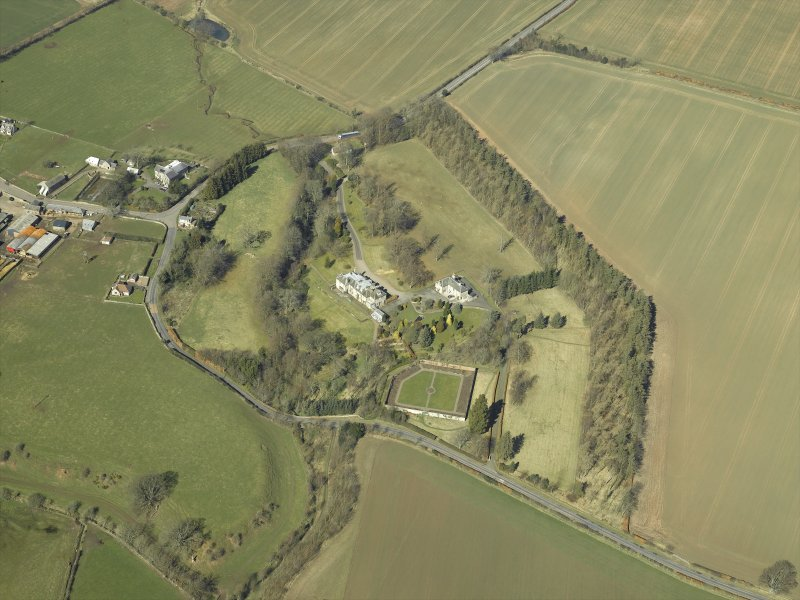 Oblique aerial view centred on the country house and walled garden with the gate-lodge and road bridge adjacent, taken from the SE.