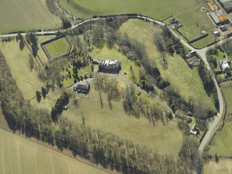Oblique aerial view centred on the country house and walled garden with the gate-lodge and road bridge adjacent, taken from the NNE.