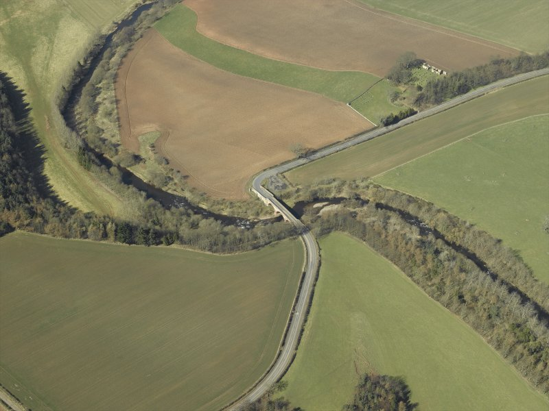 Oblique aerial view centred on the road bridge with the remains of the church and burial-ground adjacent, taken from the SE.