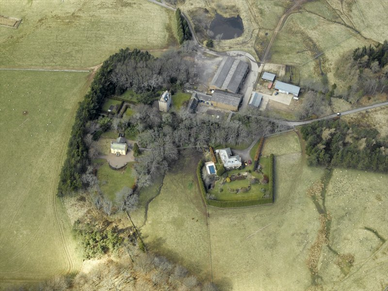 Oblique aerial view centred on the remains of the tower-house and the farmsteading, stable and farmhouse, taken from the SE.
