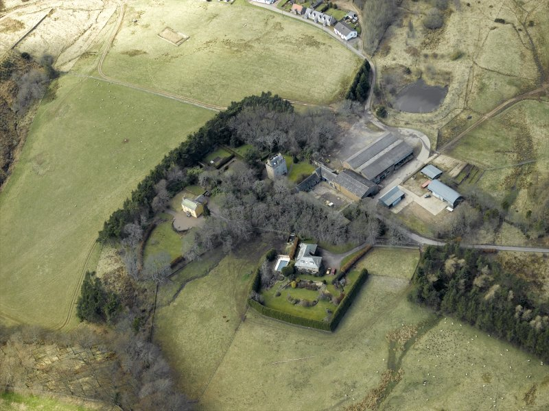 Oblique aerial view centred on the remains of the tower-house and the farmsteading, stable and farmhouse, taken from the ESE.