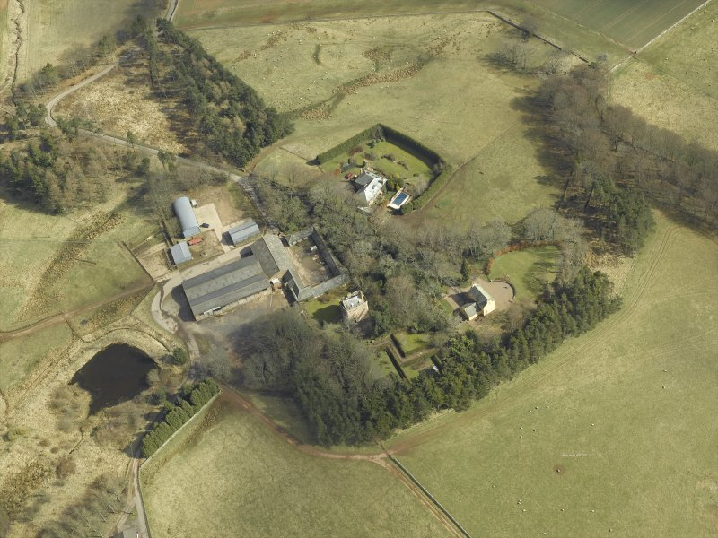 Oblique aerial view centred on the remains of the tower-house and the farmsteading, stable and farmhouse, taken from the WNW.