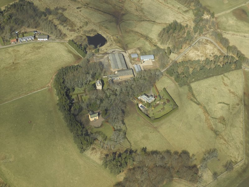 Oblique aerial view centred on the remains of the tower-house and the farmsteading, stable and farmhouse, taken from the SSW.