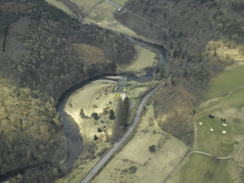 Oblique aerial view centred on the remains of the castle, outbuildings and walled garden with the railway viaduct adjacent, taken from the ENE.