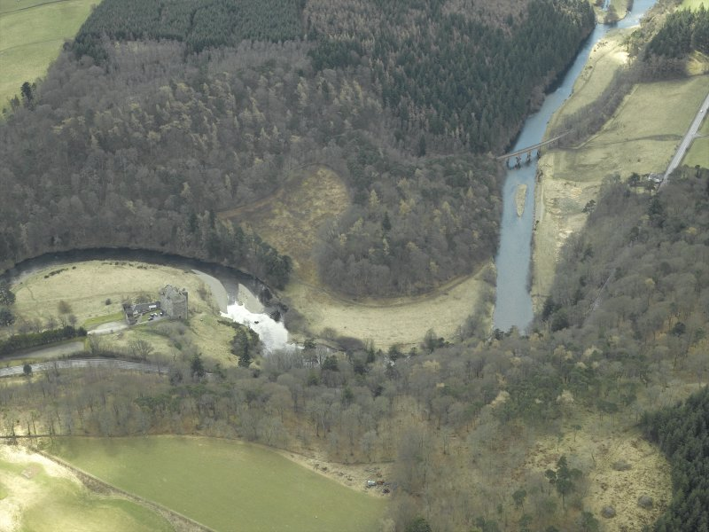 Oblique aerial view centred on the remains of Neidpath Castle, outbuildings and walled garden with the railway viaduct adjacent, taken from the NNE.