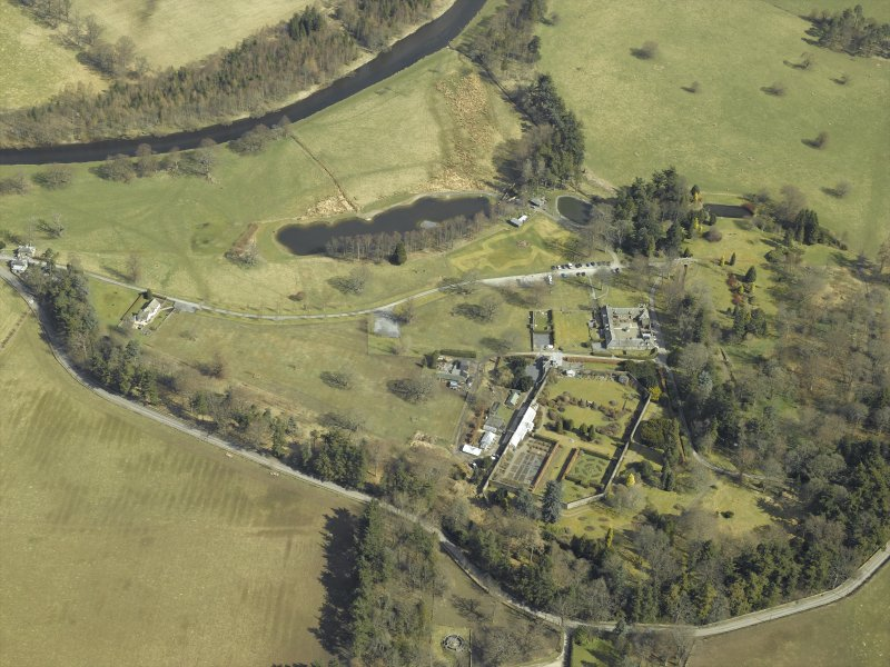 Oblique aerial view centred on the country house, gardens, walled garden and stables with the dovecot adjacent, taken from the SW.
