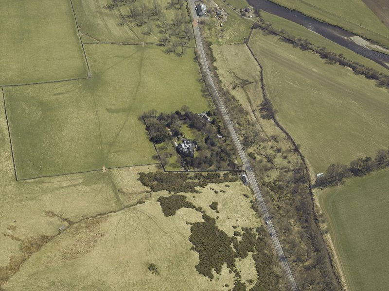 Oblique aerial view centred on the country house and landscaped garden, taken from the WNW.