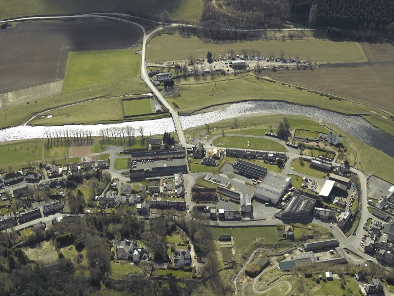 Oblique aerial view centred on the woollen mill with the road bridge and convent  adjacent, taken from the N.