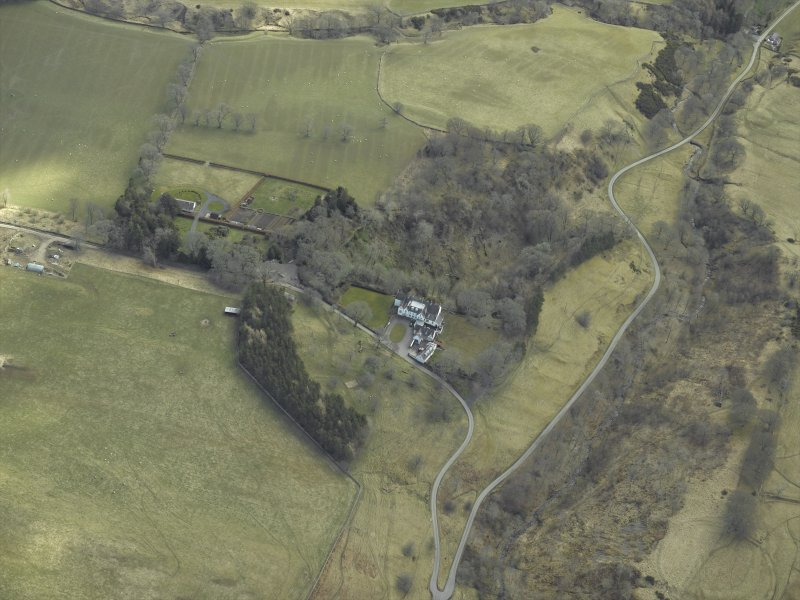 Oblique aerial view centred on country house, taken from the NW.