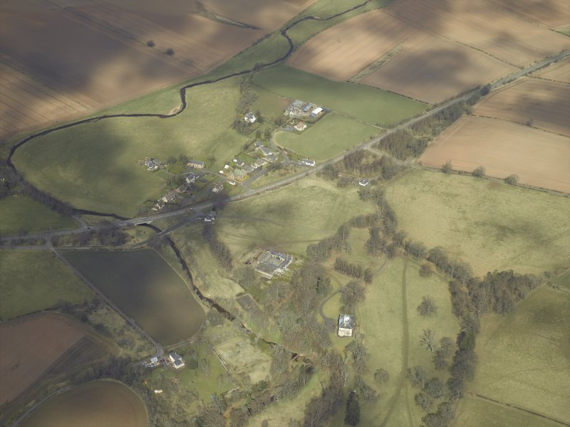 General oblique aerial view centred on the country house and stables with the gate-lodges, walled garden and village adjacent, taken from the SSW.