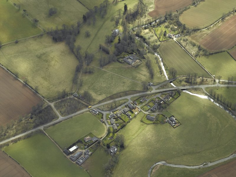 General oblique aerial view centred on the country house and stables with the gate-lodges, walled garden and village adjacent, taken from the N.