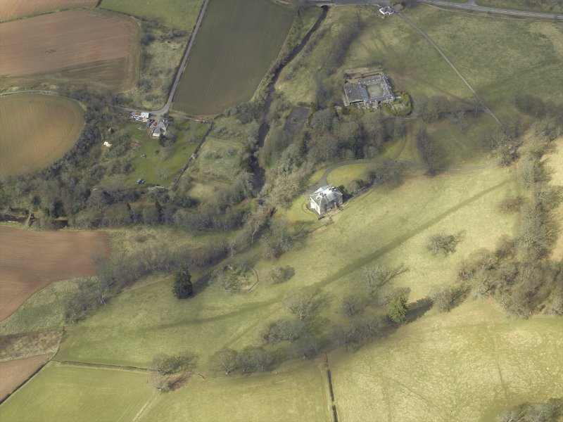 Oblique aerial view centred on the country house and stables with the gate-lodge, walled garden and the remains of the church adjacent, taken from the SE.