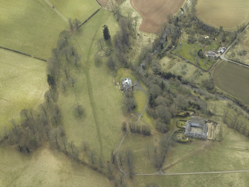 Oblique aerial view centred on the country house and stables with the walled garden adjacent, taken from the NNE.