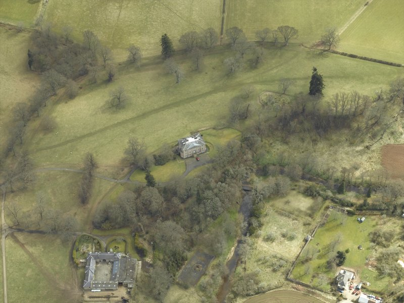 Oblique aerial view centred on the country house and stables with the walled garden adjacent, taken from the NW.