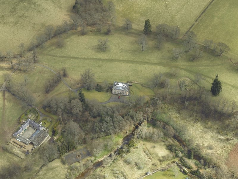 Oblique aerial view centred on the country house and stables and the remains of the church, taken from the W.