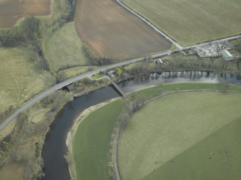 Oblique aerial view centred on the suspension bridge, farmhouse, farmsteading, cottage and road bridge, taken from the NW.