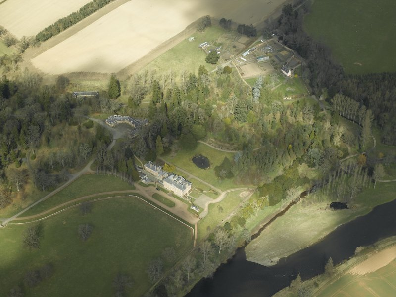 General oblique aerial view centred on the country house, stables and gardens with the house adjacent, taken from the S.