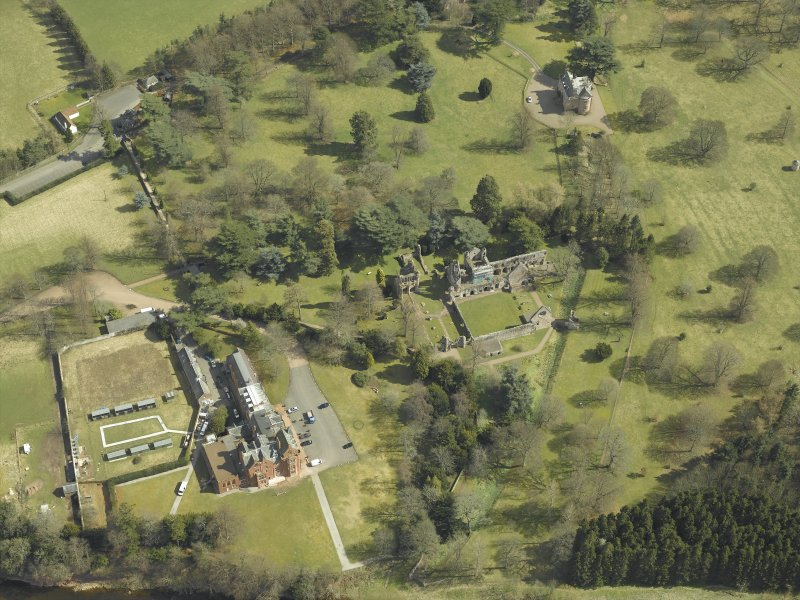 Oblique aerial view centred on the remains of the abbey with the hotel and country house adjacent, taken from the WNW.
