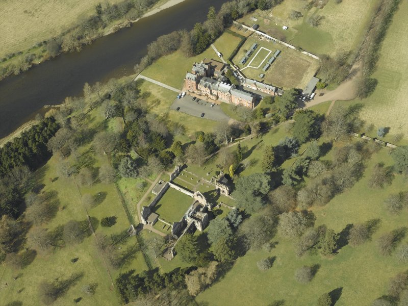 Oblique aerial view centred on the remains of the abbey with the hotel adjacent, taken from the SE.