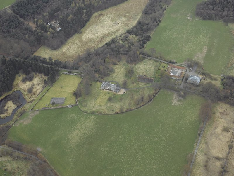 Oblique aerial view centred on the country house, walled garden, farmsteading, stables and dovecot, taken from the E.