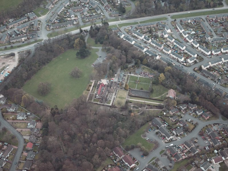 Oblique aerial view centred on the house and walled garden with the gate lodge adjacent, taken from the WSW.