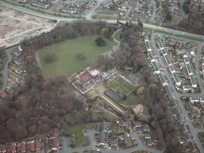Oblique aerial view centred on the house and walled garden with the gate lodge adjacent, taken from the SW.