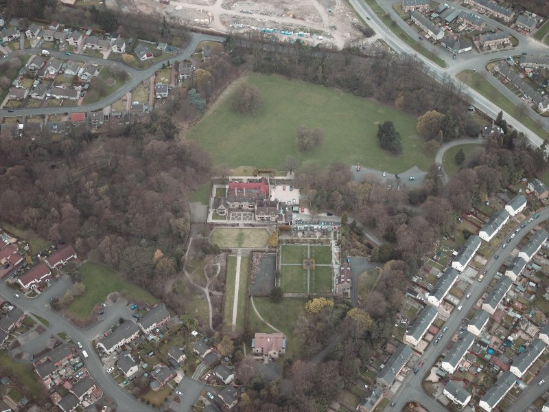 Oblique aerial view centred on the house and walled garden with the gate lodge adjacent, taken from the S.