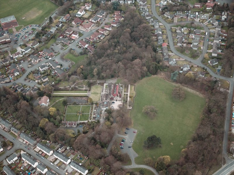 Oblique aerial view centred on the house and walled garden, taken from the NE.