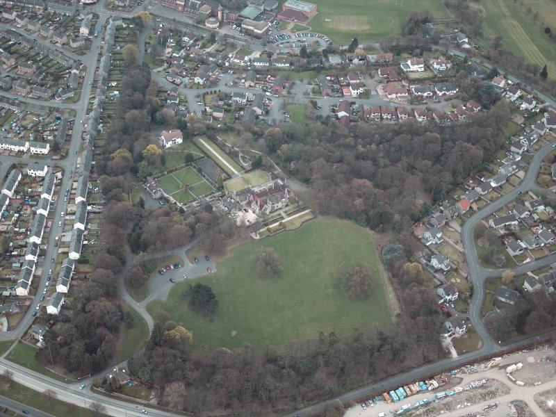 Oblique aerial view centred on the house and walled garden with the gate lodge adjacent, taken from the N.