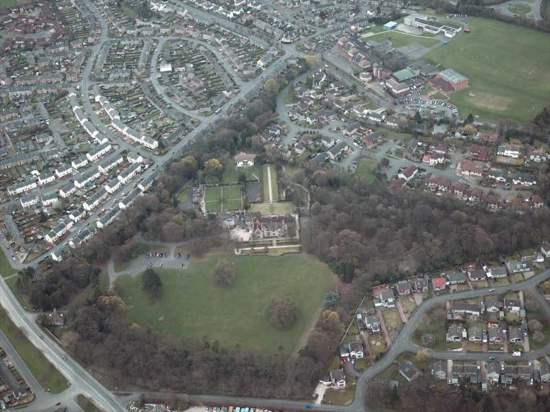 Oblique aerial view centred on the house and walled garden with the gate lodge adjacent, taken from the NW.