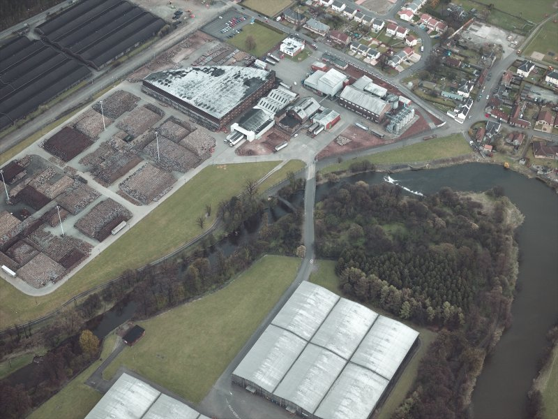 Oblique aerial view centred on the footbridge with the whisky distillery and bonded warehouses adjacent, taken from the W.