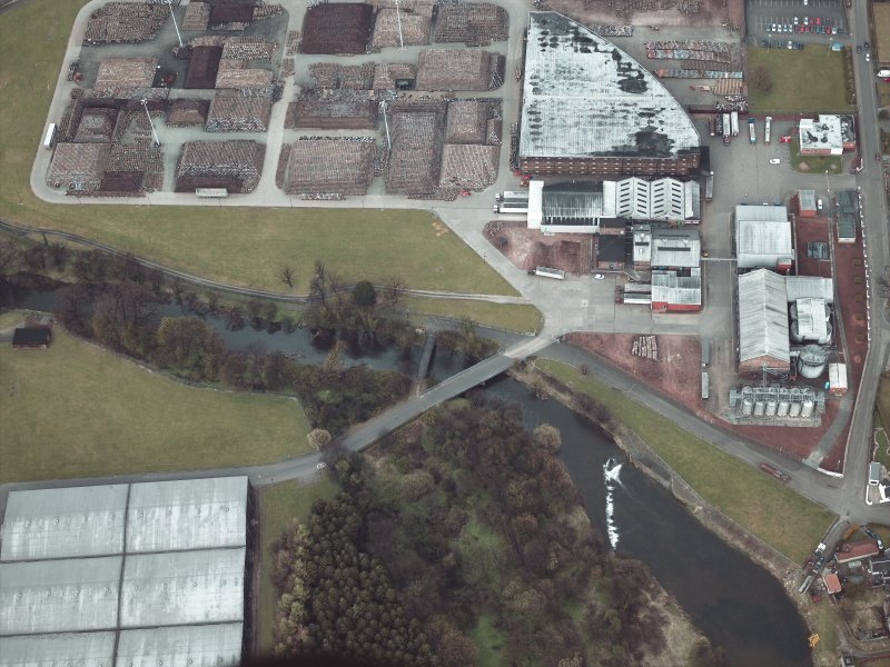 Oblique aerial view centred on the footbridge with the whisky distillery and bonded warehouses adjacent, taken from the SW.