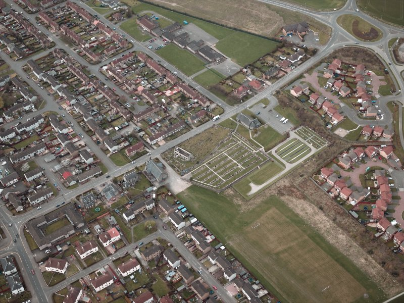 Oblique aerial view centred on the churches, burial-ground and church hall, taken from the SE.