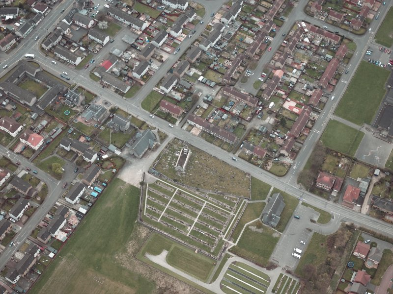Oblique aerial view centred on the churches, burial-ground and church hall, taken from the NE.
