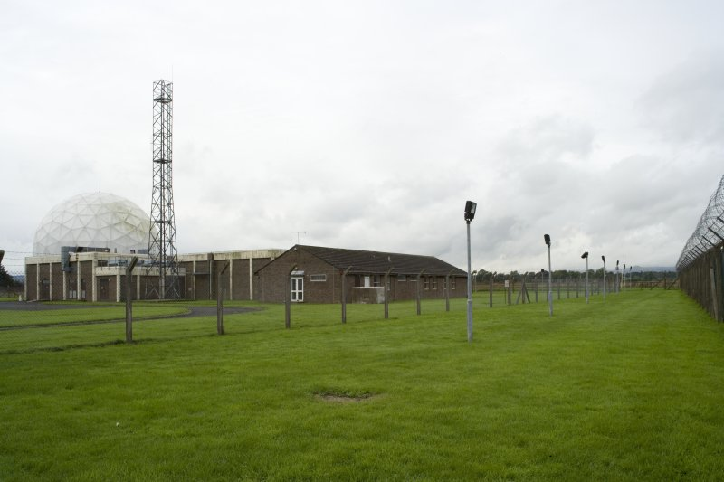View.  Main building, Radome, communication mast and part of the perimeter fence from E.