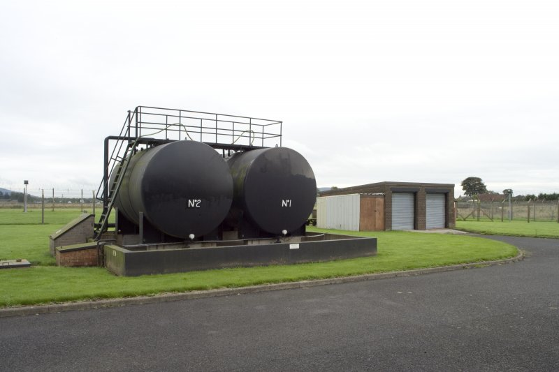 View.  Diesel fuel tanks for emergency generators with workshop/garage in background from E.