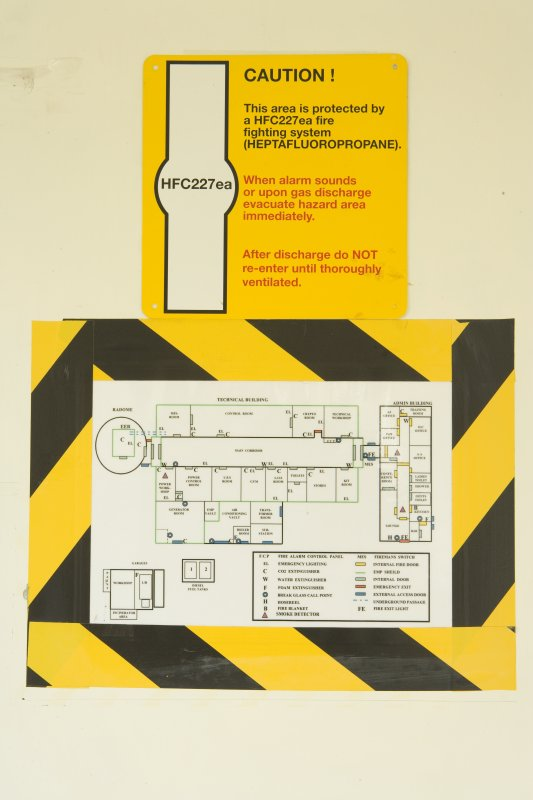 Interior.  Detail of notice in entrance hall to main building showing plan of room layout and warning sign for the use of gas for fire extinguishing.