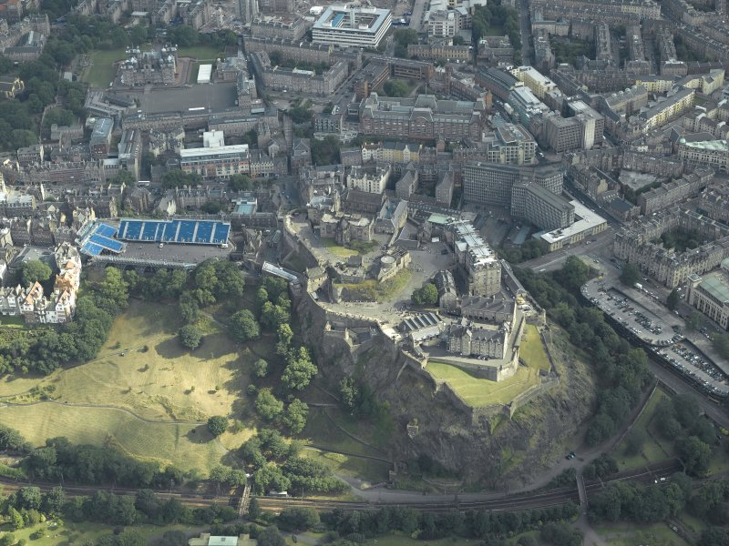 Oblique aerial view centred on the castle with the Military Tattoo stands set up on the esplanade and the school adjacent, taken from the NW.