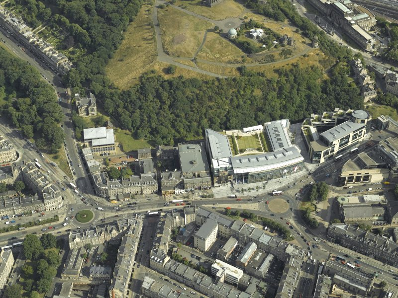 Oblique aerial view of Edinburgh centred on Calton Hill and Greenside Place with the hotel, cinemas, theatre, observatories and church, taken from the NW.