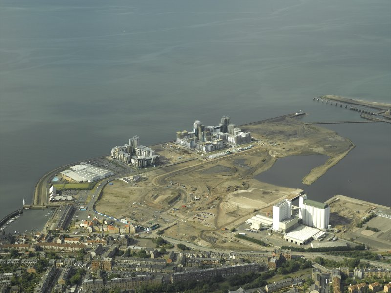 Oblique aerial view centred on the construction of the flats with the shipbuilding yard in the foreground, taken from the S.