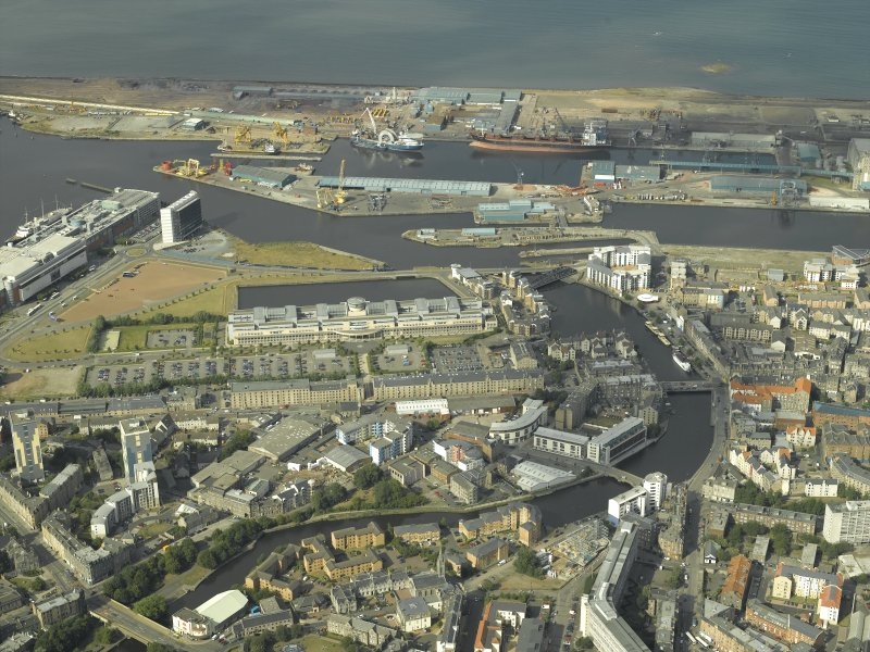General oblique aerial view centred on the offices, road bridges, swing bridge, harbour, dock and shed, taken from the SW.